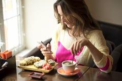 女孩,坐在与咖啡的一个咖啡馆 库存照片