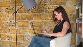 女孩,女实业家与膝上型计算机一起使用,坐在与灯的一把椅子 学生为检查做准备 影视素材