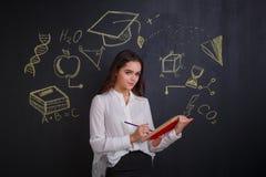 女孩,铅笔标记某事在一本开放书,站立在有科学的图象的一个委员会附近签字 库存照片