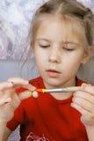 女孩绘一个自制玩具 免版税图库摄影