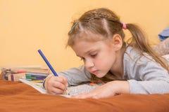 女孩画一坚硬说谎在他的有一支铅笔的胃在纸 库存图片