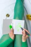 女孩以画三叶草的绿色 库存照片