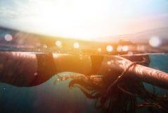 女孩水下与太阳光芒 免版税库存图片
