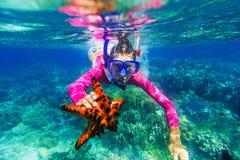 女孩水下的照片有海星的 免版税库存图片