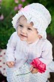 女孩8个月步行的欧洲乌克兰矮小的婴孩在庭院拿着一朵花和草莓在她的手上 图库摄影