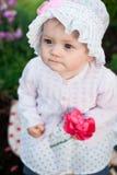 女孩8个月步行的欧洲乌克兰矮小的婴孩在庭院拿着一朵花和草莓在她的手上 免版税库存图片