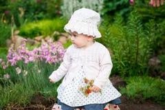 女孩8个月步行的欧洲乌克兰矮小的婴孩在庭院拿着一朵花和草莓在她的手上 免版税图库摄影