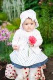 女孩8个月步行的欧洲乌克兰矮小的婴孩在庭院拿着一朵花和草莓在她的手上 库存图片