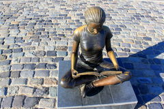 女孩读书古铜色雕象  库存图片