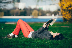 女孩读书在公园 免版税库存图片