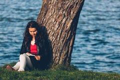 女孩读书在公园 库存图片