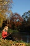女孩读书在秋天公园 库存图片