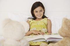 女孩读书对她的玩具熊的故事书 免版税库存照片
