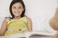 女孩读书对她的玩具熊的故事书 免版税库存图片