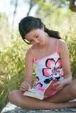 女孩读书平装书 免版税库存图片