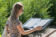 女孩读书餐馆菜单 图库摄影