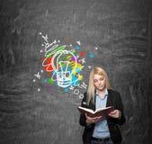 女孩读书,有色的图象的黑板在backgr 免版税库存照片