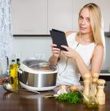 女孩读书ereader和烹调与新的crockpot 免版税库存图片