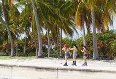 女孩滚动在晴朗的Crandon公园海滩 图库摄影