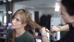 女孩头发理发illusration长的沙龙向量 头发的专家堆积党的女孩 美发师通过做小环 股票录像