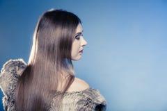 女孩头发长的纵向 皮大衣的少妇在蓝色 免版税库存照片