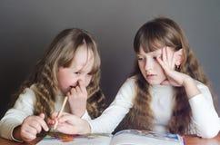女孩读和一个采摘他的鼻子 图库摄影