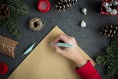 女孩给圣诞老人的文字信件与在黄色纸的墨水笔在与圣诞节装饰的灰色背景 免版税库存照片