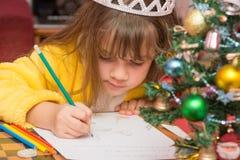 女孩画在信件的一张图片给圣诞老人 免版税库存图片