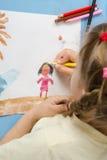 女孩画在图画被绘的颜色的一支铅笔 库存照片