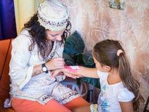 女孩绘在孩子的胳膊的耐洗的纹身花刺 库存图片