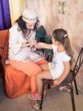 女孩绘在孩子的胳膊的耐洗的纹身花刺 免版税图库摄影