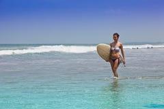女孩去在海洋海岸的比基尼泳装与海浪的一个委员会 库存图片