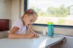 女孩画在纸片的一支笔在一个第二等的火车支架的 免版税库存图片