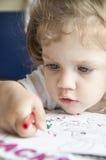 女孩画在纸片的一支铅笔 免版税库存图片