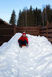 女孩从在茶碟的雪小山滑下来 免版税库存照片