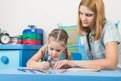 女孩画在铅板的兴趣,一个女孩帮助她 库存图片