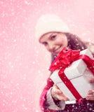 女孩给在雪的圣诞节礼物 免版税库存照片
