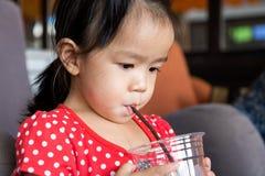 女孩从塑料玻璃的饮料水 库存照片