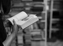 女孩从她射击的阅读书  免版税库存照片