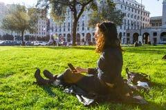 女孩/学生放松和享用太阳的绿草草坪的 免版税库存照片