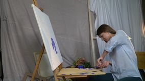 女孩画家从在一个木调色板的tbe紧压红色油漆在站立的帆布前面坐画架 股票录像