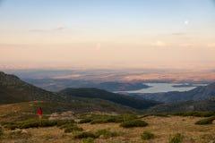 女孩登山人冥想一惊人的日落和月出 免版税库存图片