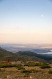 女孩登山人冥想一惊人的日落和月出 库存照片