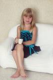 女孩5岁坐有杯子的一个沙发 免版税图库摄影