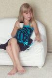 女孩5岁坐有杯子的一个沙发 免版税库存图片