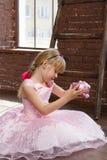 女孩6岁有存钱罐的桃红色礼服在他的手上 垂直构筑 免版税库存照片