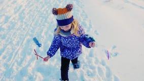 女孩5岁获得跑在雪的乐趣,做滑稽的面孔,笑 股票视频