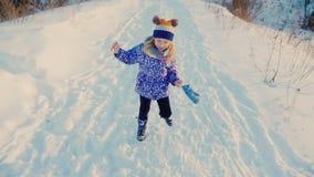 女孩5岁获得跑在雪的乐趣,做滑稽的面孔,笑 影视素材