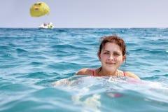女孩19岁,在单独蓝色海水的游泳 库存图片