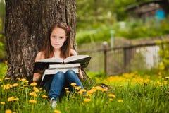 女孩11岁读一本书 免版税图库摄影